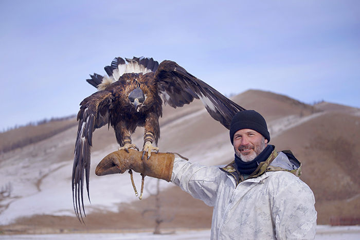 Joel Lambert holding an eagle in Mongolia.