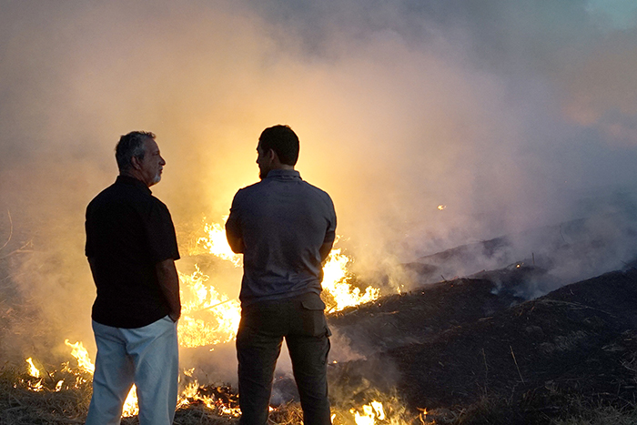 Retired Detective Rhodes Sanchez and Detective Aubrey St. Angelo speaking by burning field.